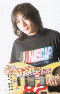 Jun Senoue holding his guitar.
