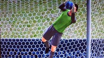The goalkeeeper at the goal, saving a soccer ball.