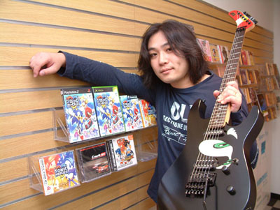 Jun with his guitar and the cover for Sonic Heroes.