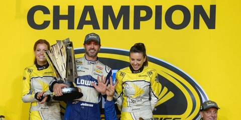 Johnson gets help from a crew member to hold up 7 fingers to celebrate his 7th Championship