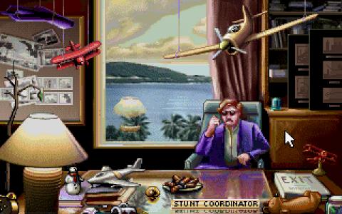 The Stunt Coordinator. Smug, behind a desk.