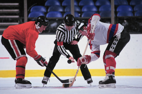 The referee drops the puck in a face-off and the game begins!